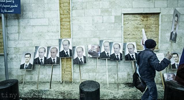 Photos of Assad and Russia's Putin are seen during a pro-Assad protest in front of the Russian embassy in Damascus, Syria