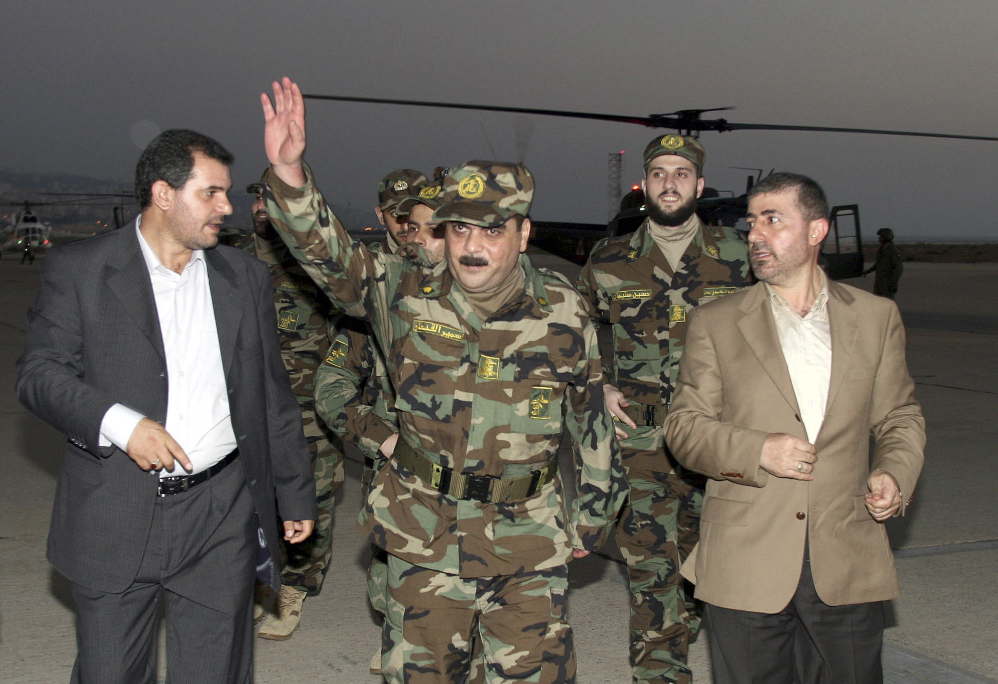 Lebanese and Hezbollah officials escort Samir Qantar (C) and the other released Lebanese prisoners upon their arrival at Beirut airport